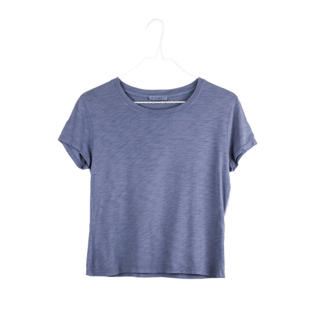 Front view of It Is Well's slate blue tee hanging on a hanger.