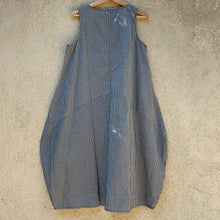 Back view  of the Tulip grey striped dress hanging on a hanger.