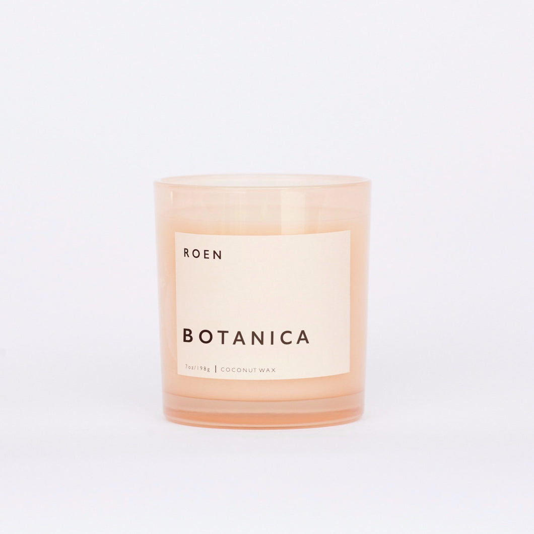 Front facing shot of Roen's Botanica scented candle in a pink glass jar with a light pink label and black font reading