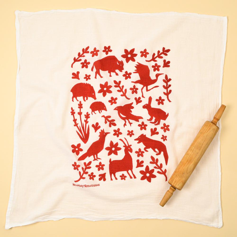 Photograph of a dishtowel with animals and plants printed on it in red.