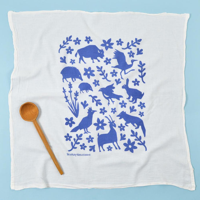 Photograph of a dishtowel with blue animals and flours printed on it.
