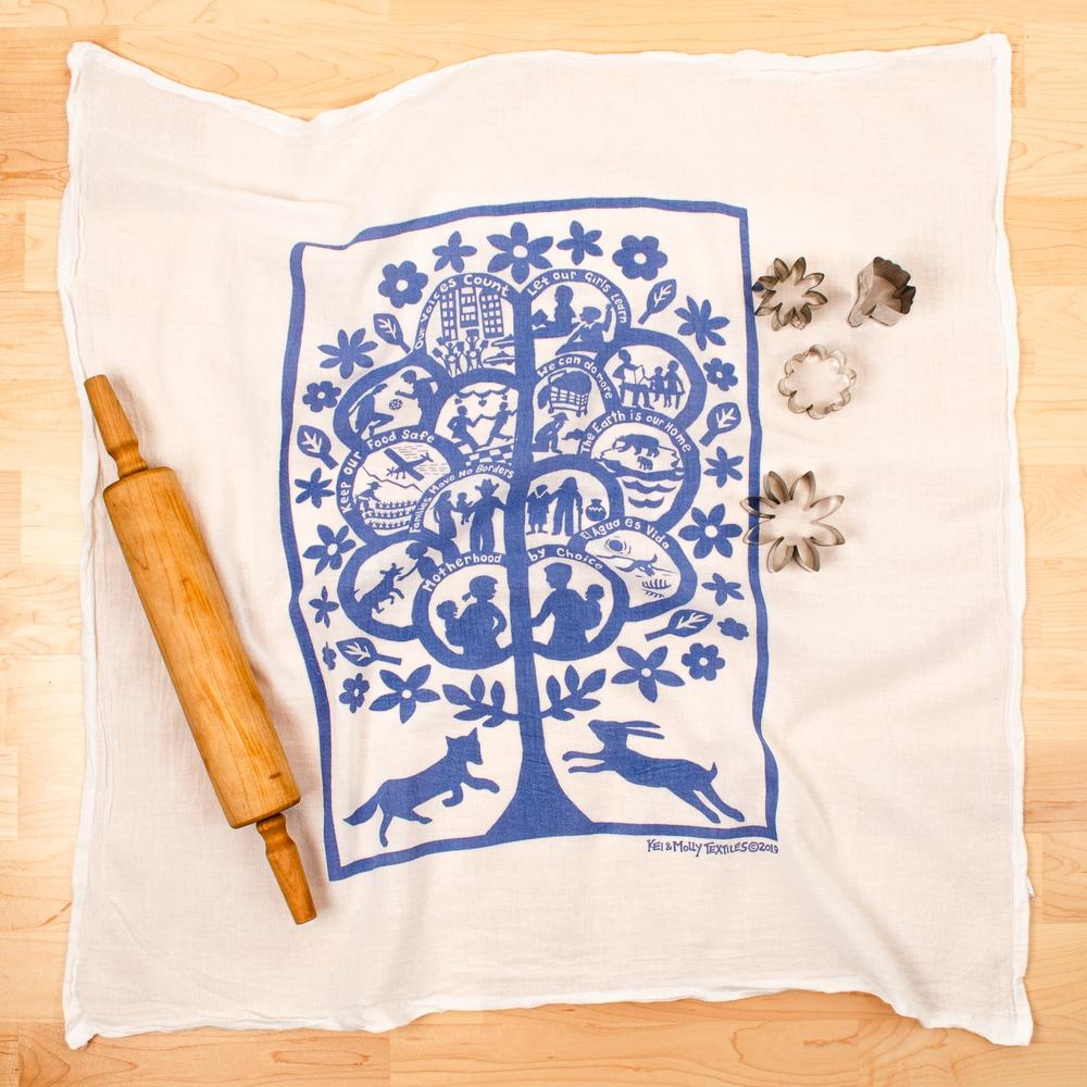 Photograph of a dishtowel printed with a blue tree, people and animals and the words,