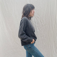 Load image into Gallery viewer, side view of model with her hands in her jean pockets wearing SWTR's grey mock neck sweater