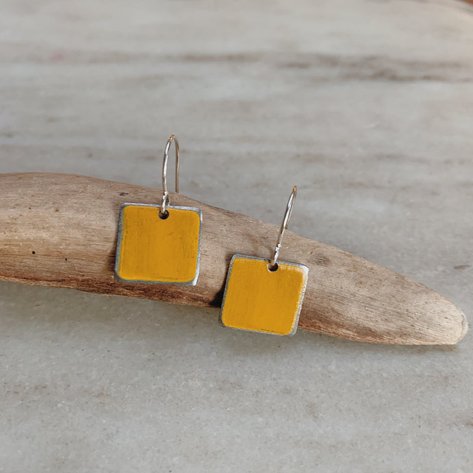 Ella Jude earrings made of painted yellow steel resting on a piece of driftwood.