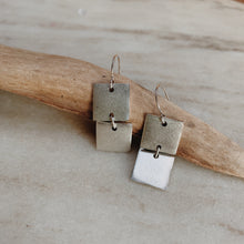 "1/2"" squares stacked between sterling silver jump rings resting on a piece of driftwood."