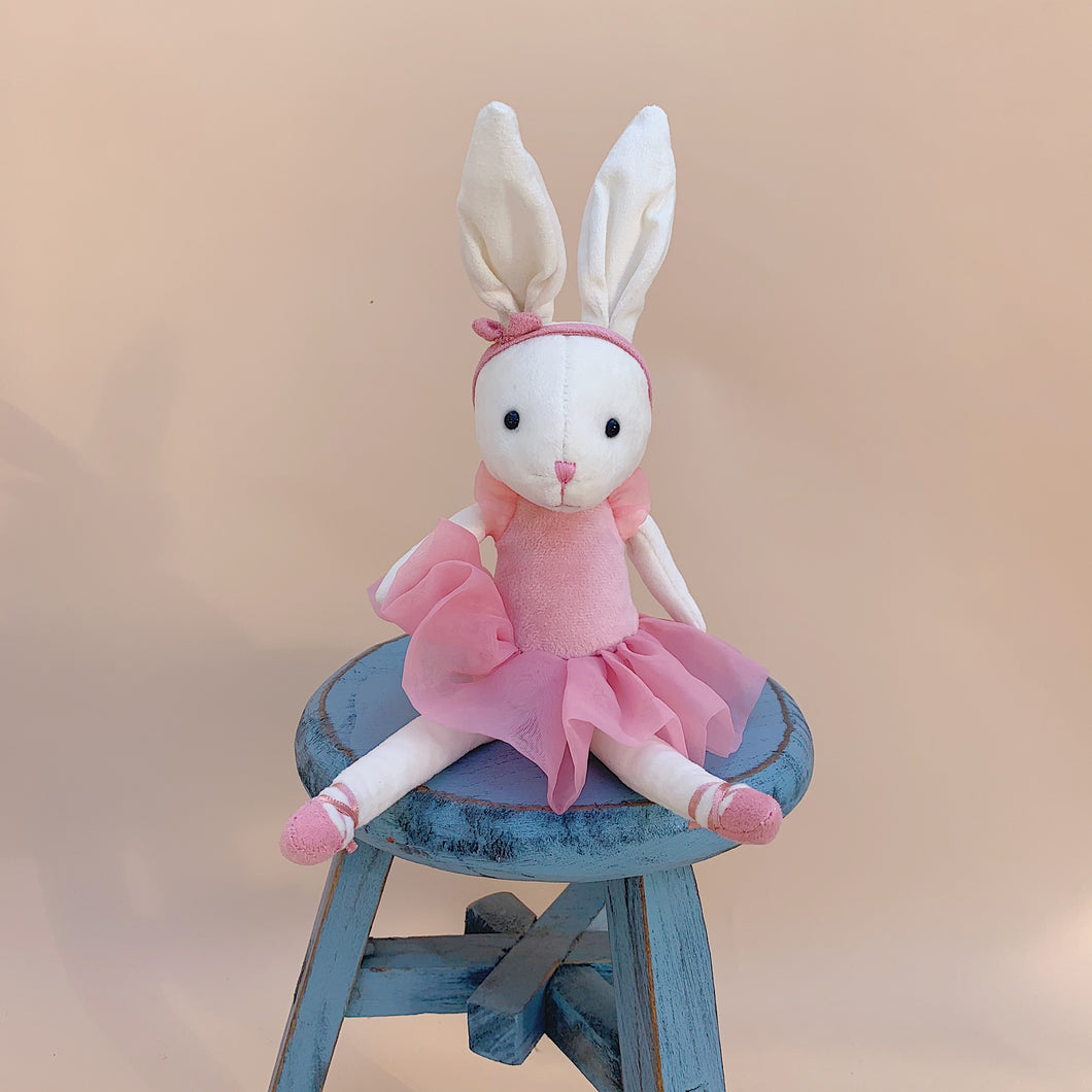Pirouette Bunny Rose front view sitting on stool with peach background front view