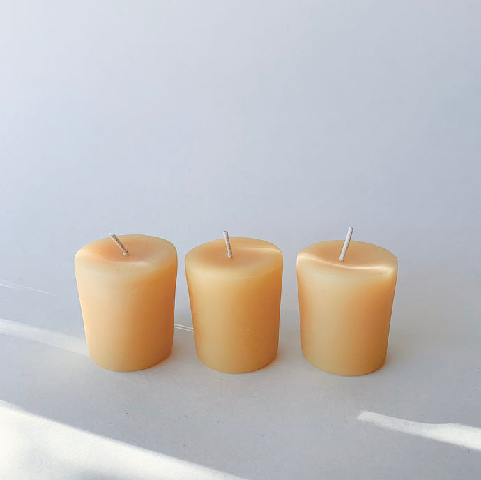 Three naturally golden beeswax votive candles arranged in a row.