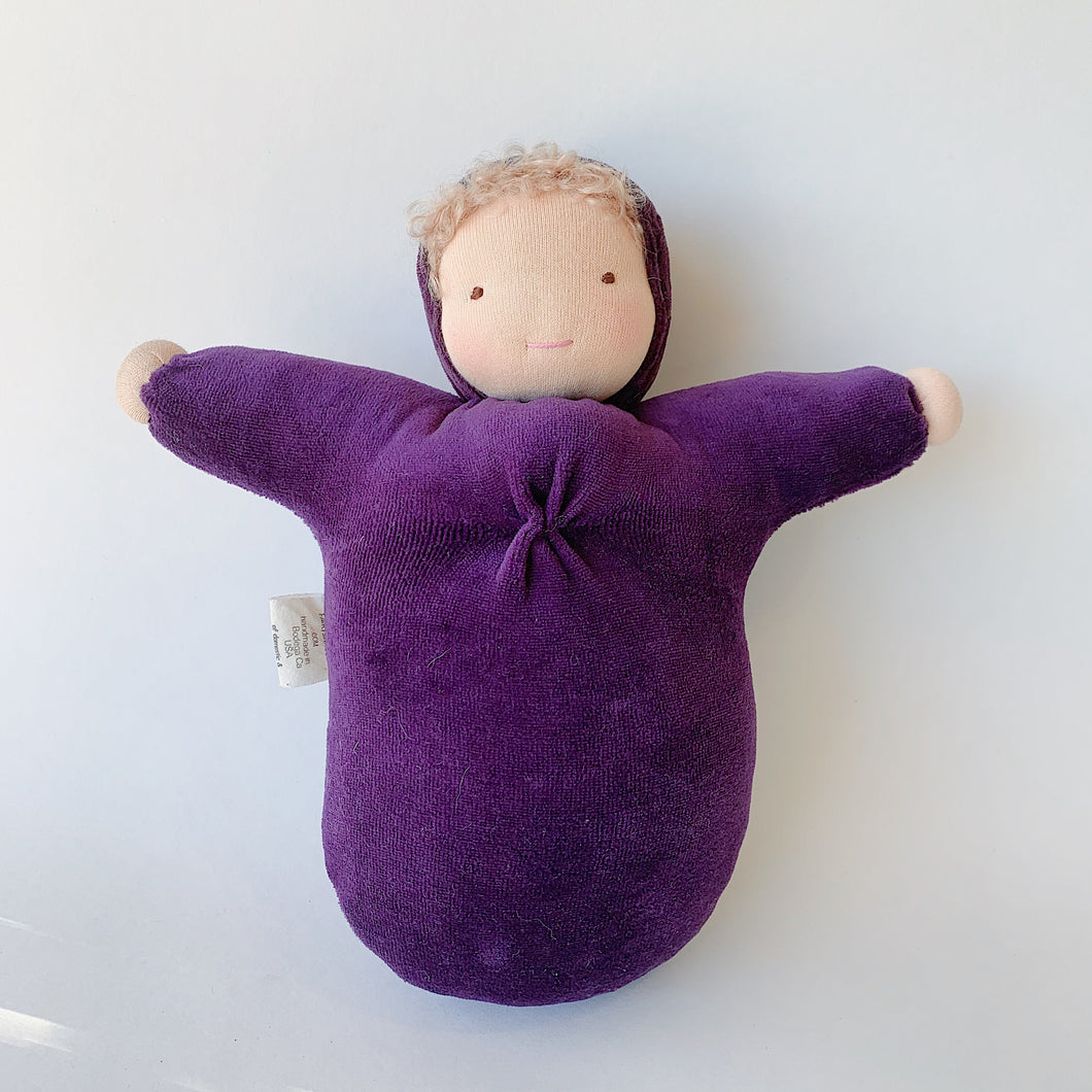 This waldorf doll is 10 inches tall with curly blond hair, light skin and a deep purple velour body.
