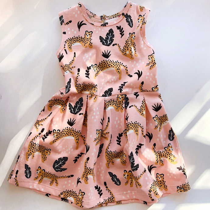 A toddler dress printed with bold gold spotted leopards and black leaves on pink fabric lying flat on a white background.