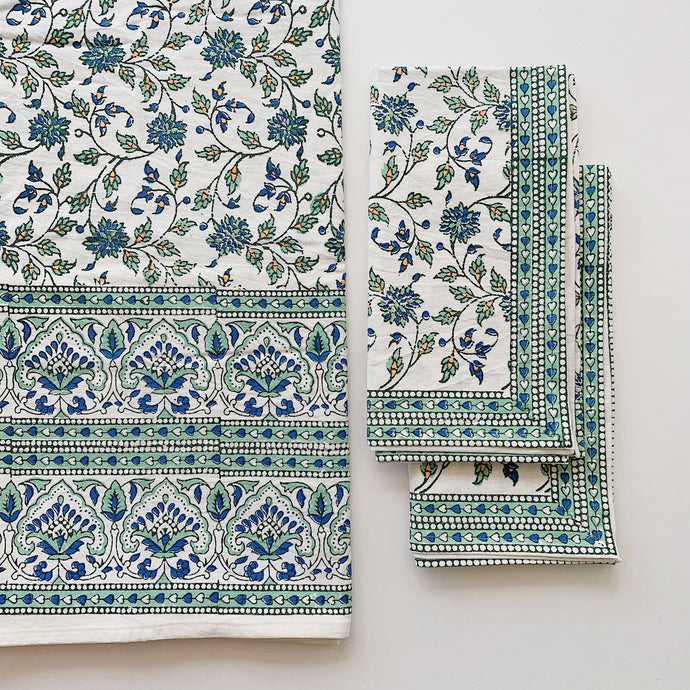 Overhead view of the Marseille Garden tablecloth featuring a green and blue floral pattern. Two napkins are lying on top of each other next to a folded tablecloth.