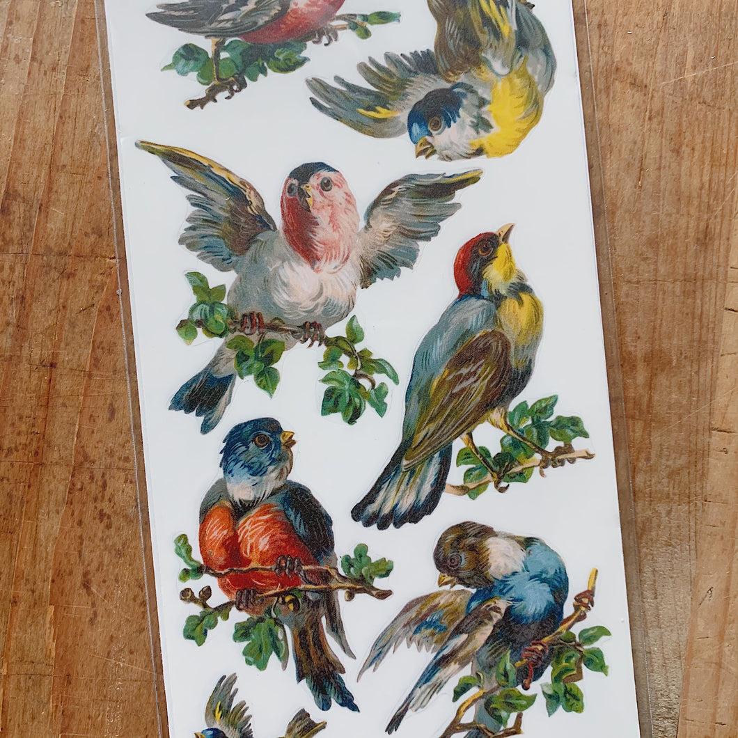 Overhead close up view of stickers of colorful swallowtail birds perched on branches and in flight