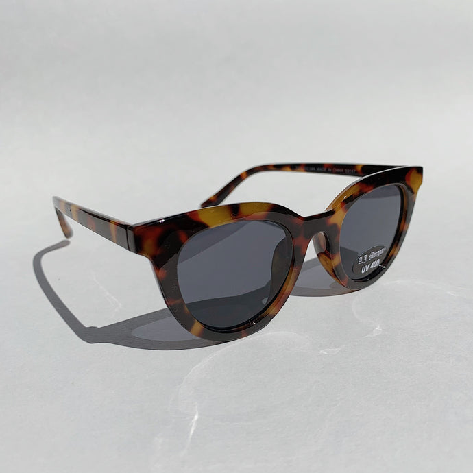 cat eye tortoiseshell sunglasses laydown front view on white background