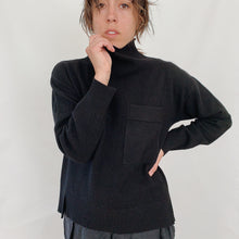 Load image into Gallery viewer, Close up of model pinching the neckline of her sweater towards her face and wearing black linen pants and SWTR's black cashmere turtleneck sweater featuring a breast pocket.