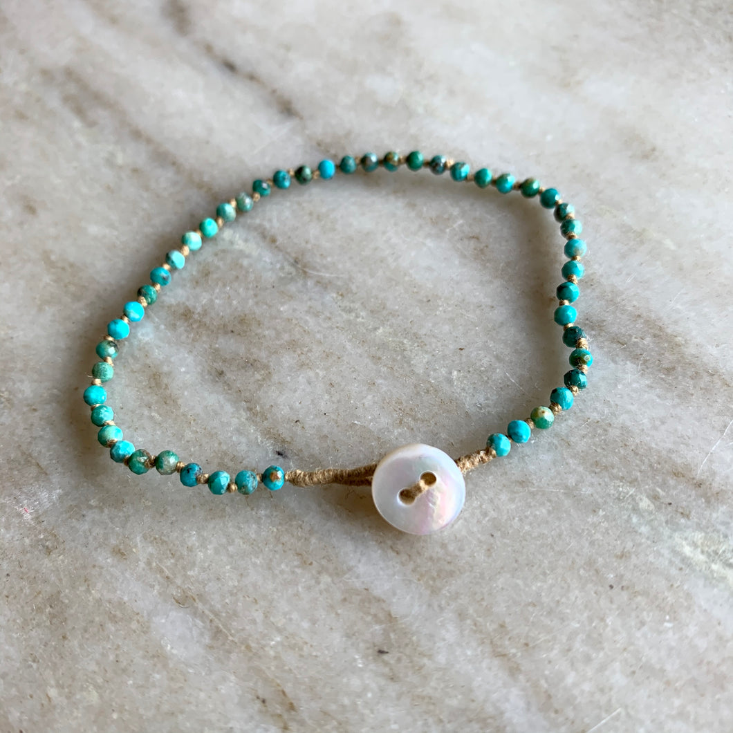 Side view of Lena Skadegard turquoise beaded bracelet with button closure.