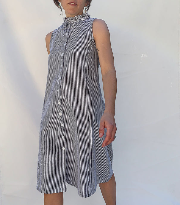 front view of model in the Giselle dress in a small grey stripe with a neck ruffle detail.