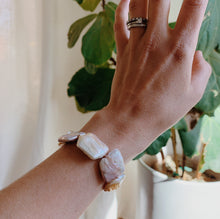 Load image into Gallery viewer, A hand runs diagonal across the photo highlighting the pearl bracelet tied around the wrist. A fig tree is in the background.