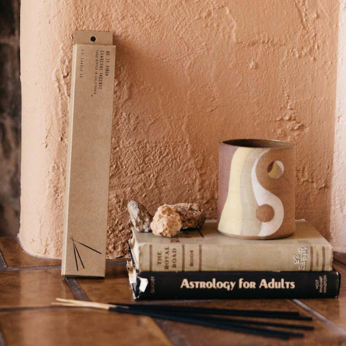Pinon incense resting next to a stack of books and ceramic mug.