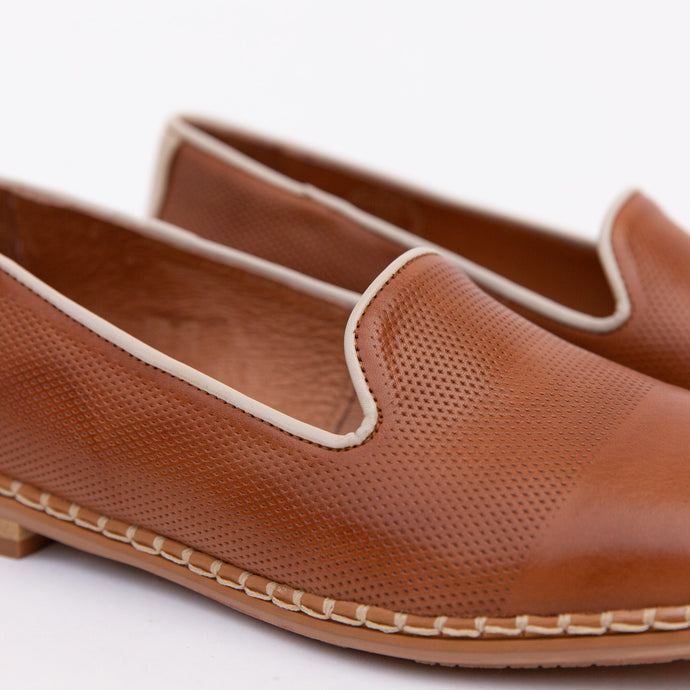 detail of perforated flat in tan and cream