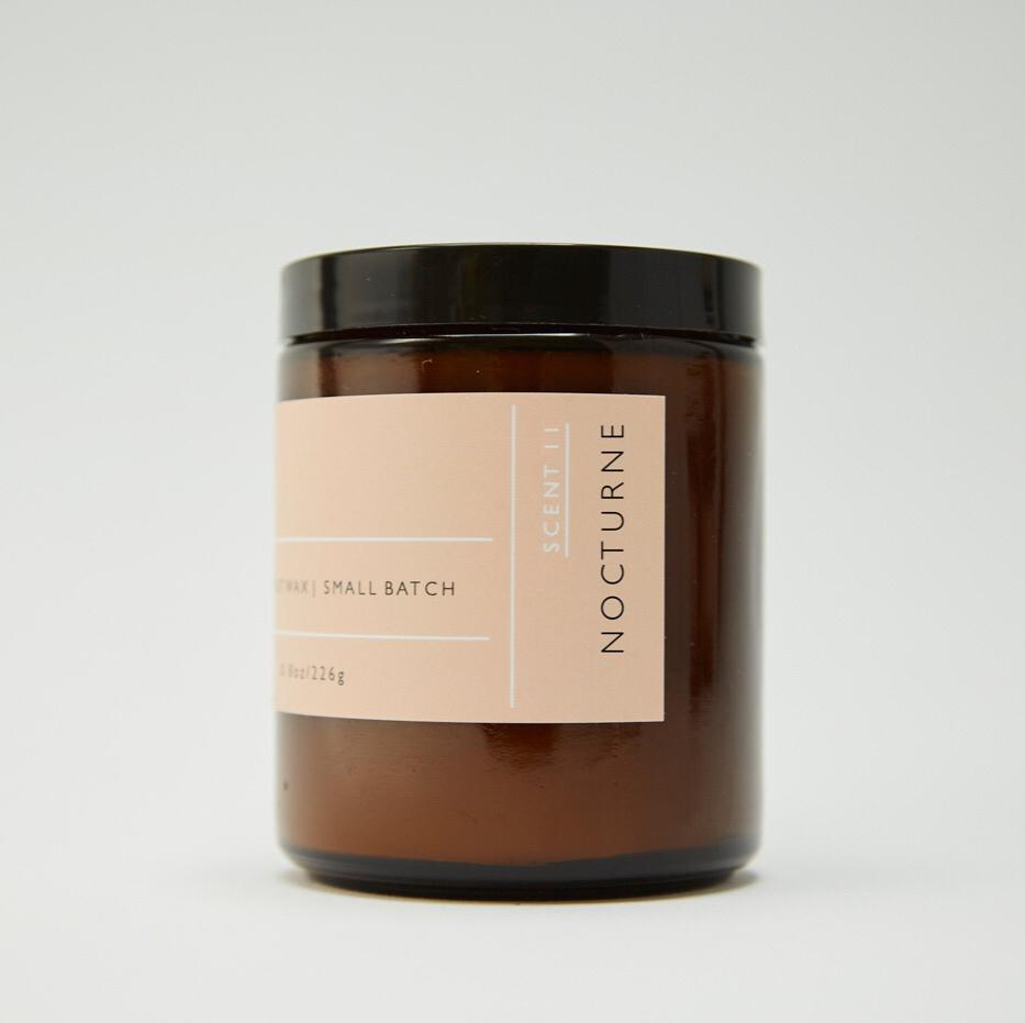 Side view of Roen's Nocturne scented candle in an amber brown glass jar with a black lid and pink label.