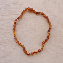 Load image into Gallery viewer, top view amber brown oval teething necklace laydown top view
