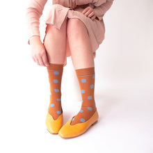 photo shows a close up of brown and blue polka dot socks worn with a pink dress and yellow shoes. The model in the picture is reaching down to touch the sock.