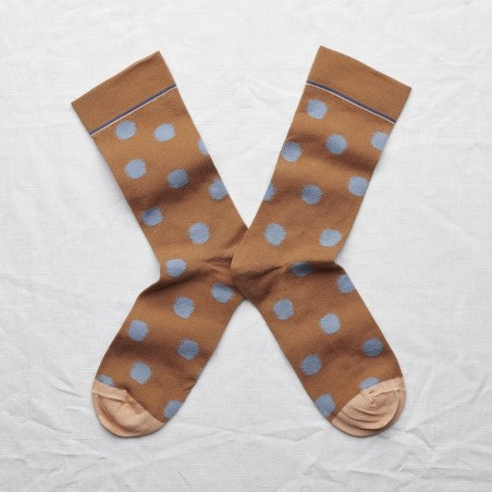Photo shows the mid-calf socks in caramel with storm blue polka dots and adobe orange toes lying flat heel to heel.