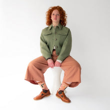 Photo shoes model sitting wearing the beige socks worn under peach pink pants and chestnut brown Mary Jane shoes.