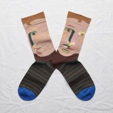 Mid-calf socks lying flat together in colors of nude beige, peach pink, spruce green with a cobalt blue toe.