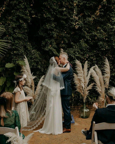 Bride kisses husband wearing Juliet cap veil
