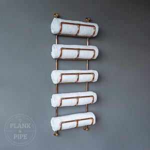 Copper towel rack holding 5 white towels