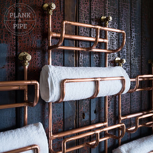 Close up of top  of copper Towel Rack holding towels