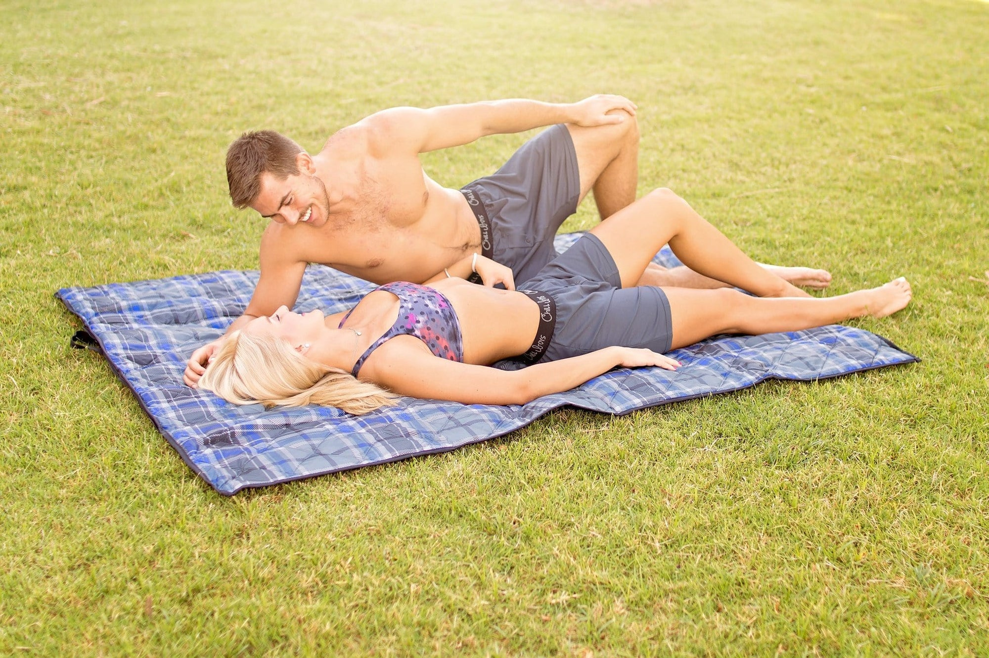 Guy and girl wearing chill boys boxers while laying on blanket
