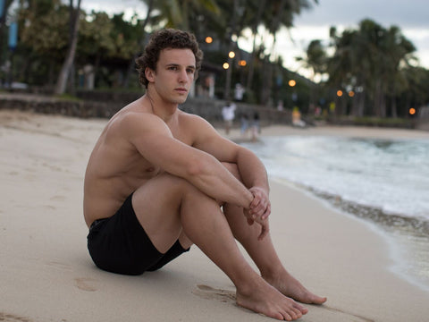 male model sitting on beach in black men's boxers