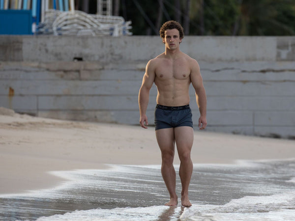 fit male model walking on beach in grey boxers