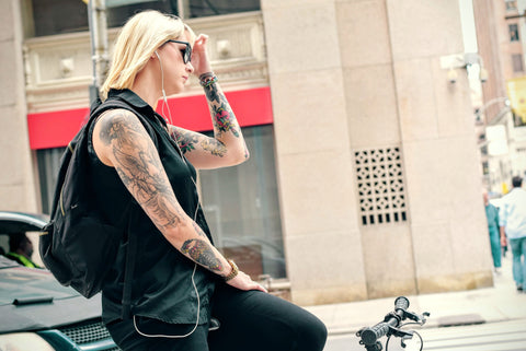 girl holding head on bike tattoed