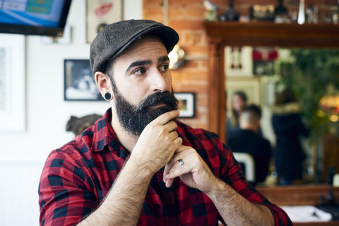 bearded man stroking beard with plugs and flannel shirt
