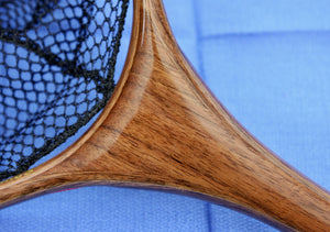 Close up of landing net handle with dark colored wood.