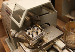 Lathe with brass rod being turned into a brass bolt.