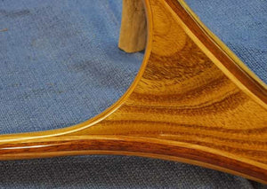 Close up of landing net handle with tan colored wood.