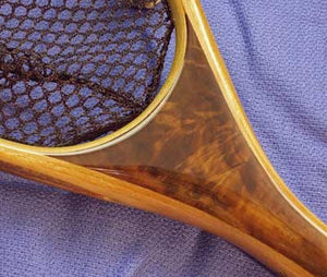 Close up of landing net handle with light and dark colored wood.