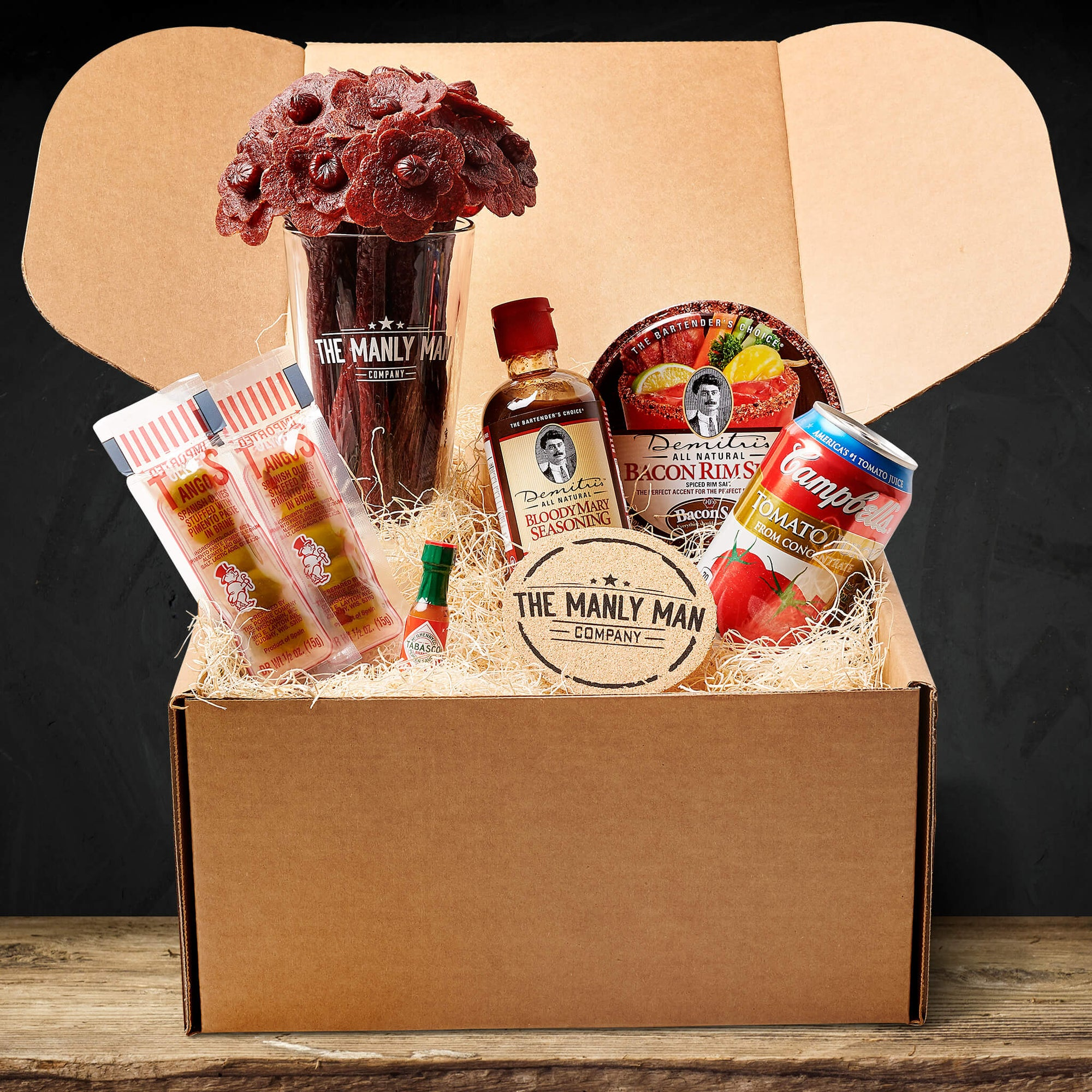 Bloody Mary kit on wood table and in front of black background, delivered as a gift for men