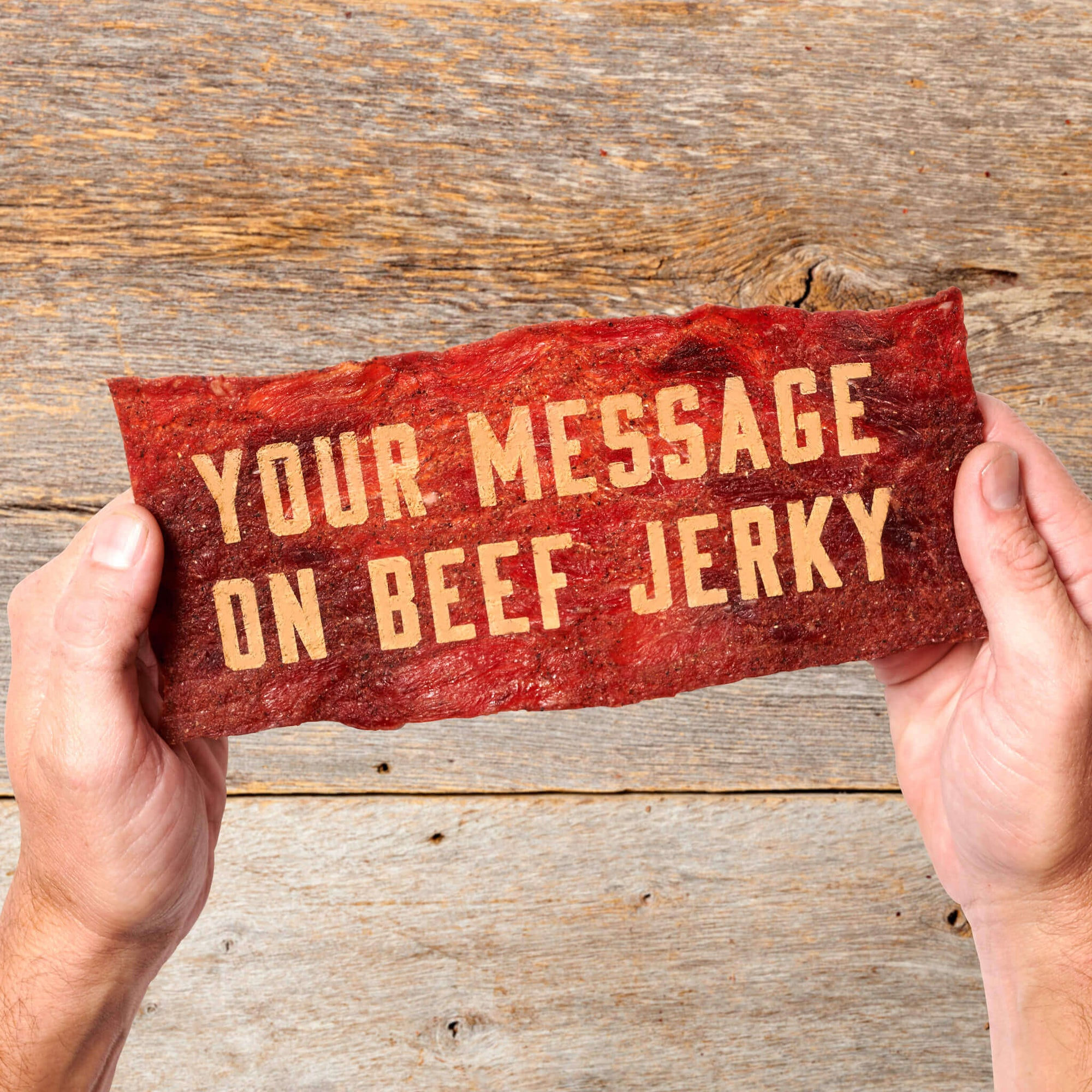 Funny gift message on custom laser engraved beef jerky greeting card being held above wood table