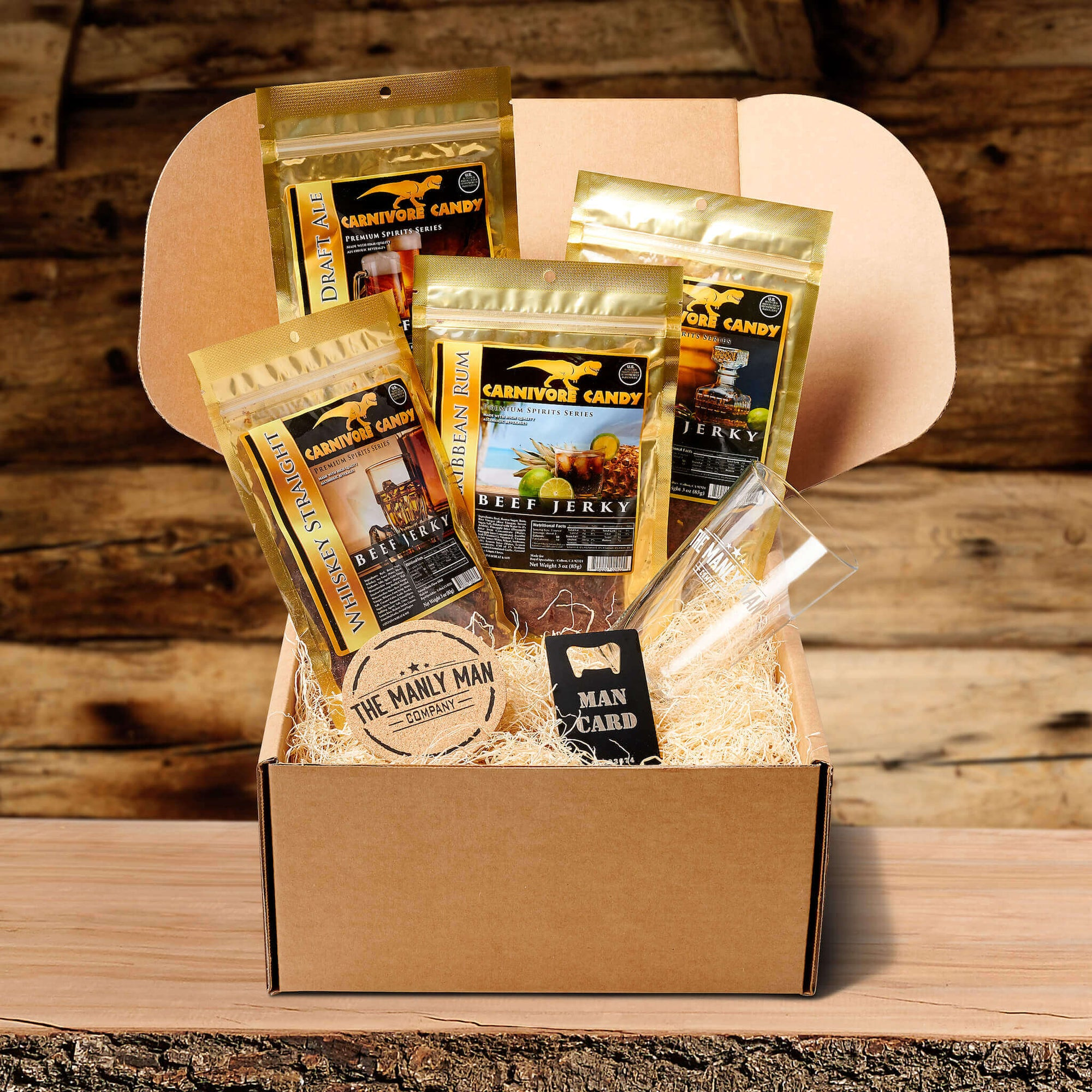 Gift crate for men, filled with alcohol-infused jerky, coaster, pint glass and man card, on log table and in front of wood panel background
