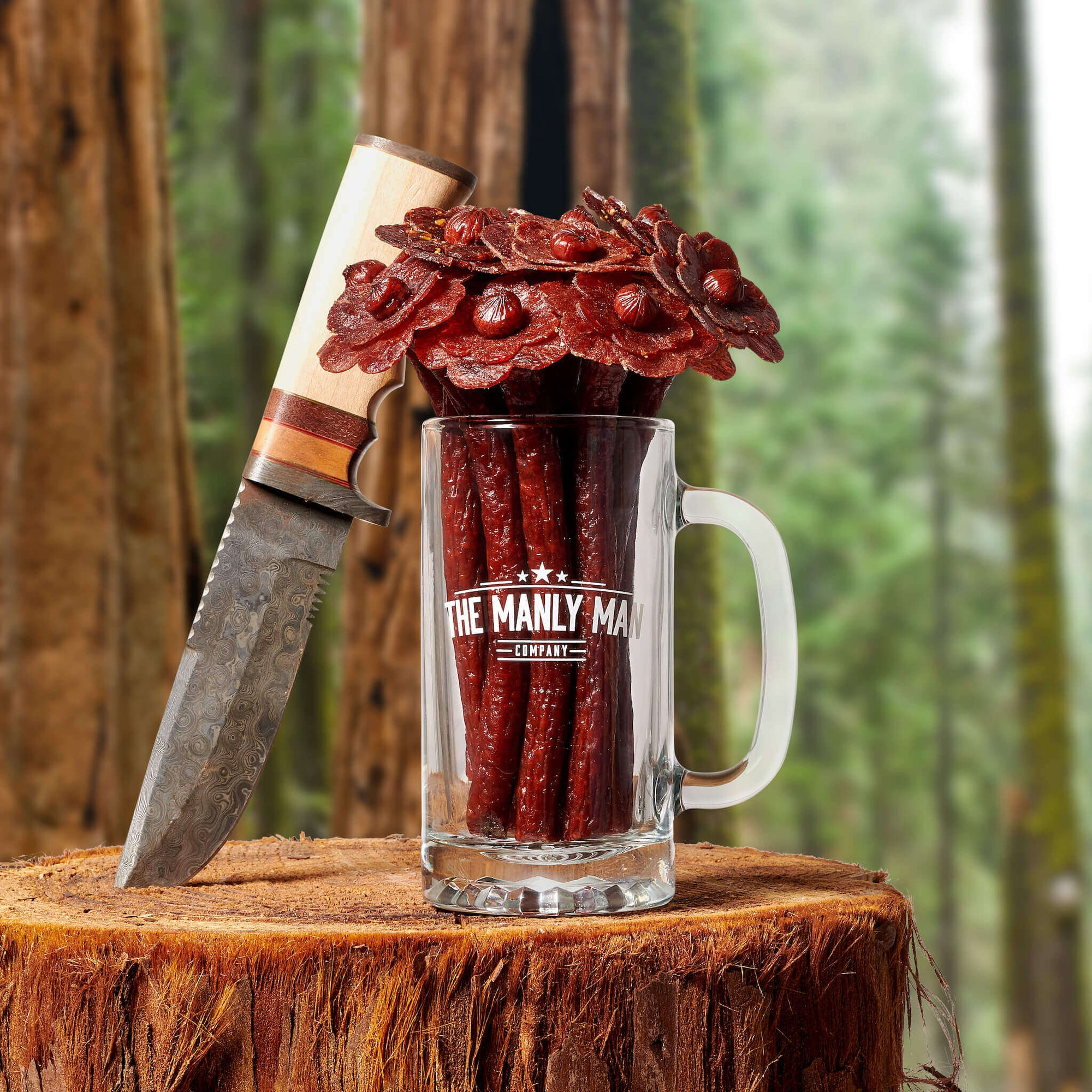 "Beef jerky flower bouquet in mug pint glass ""vase"", next to Bowie knife, on log and forrest background"