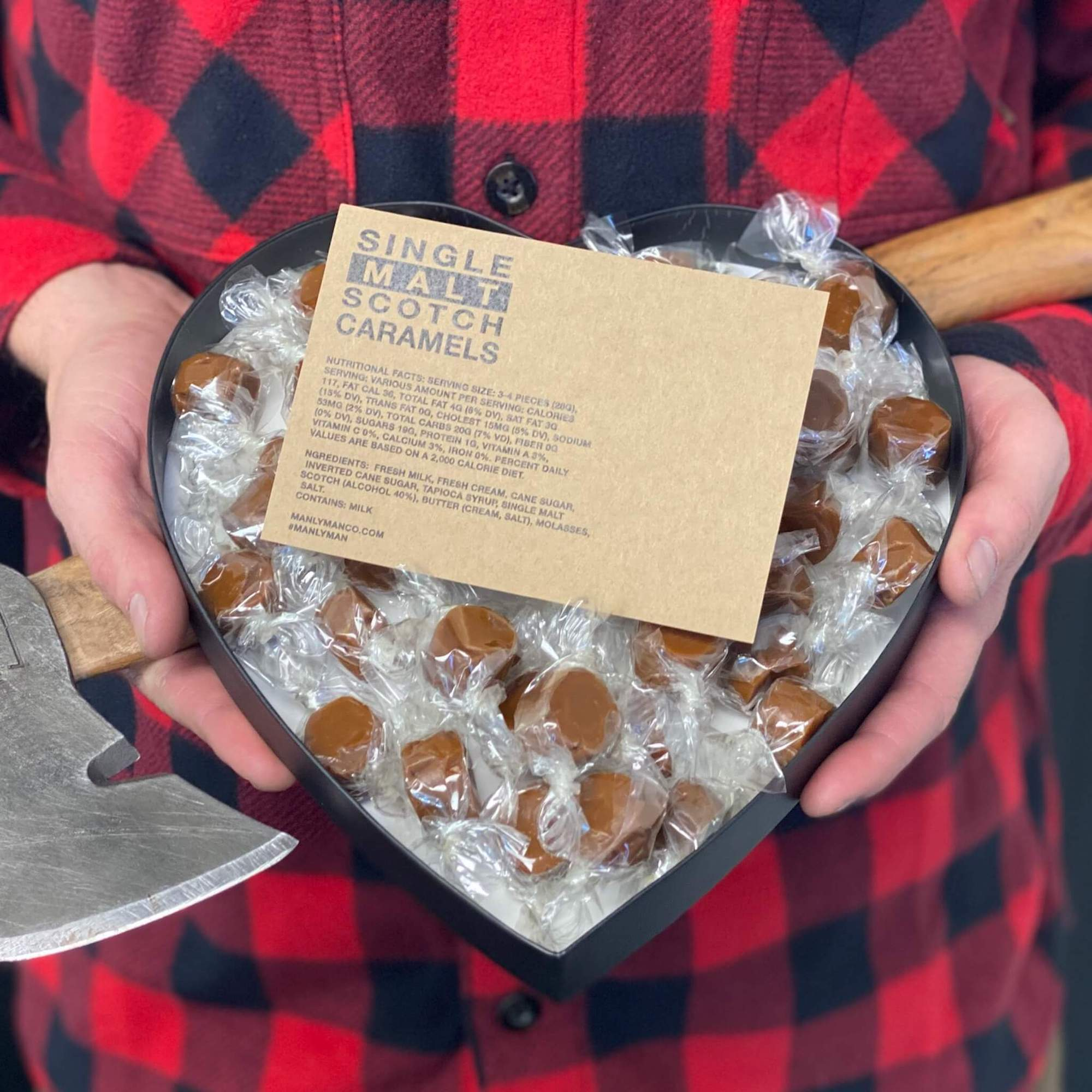 New heart-shaped gift box, filled with single malt scotch caramels, being held by man in flannel shirt