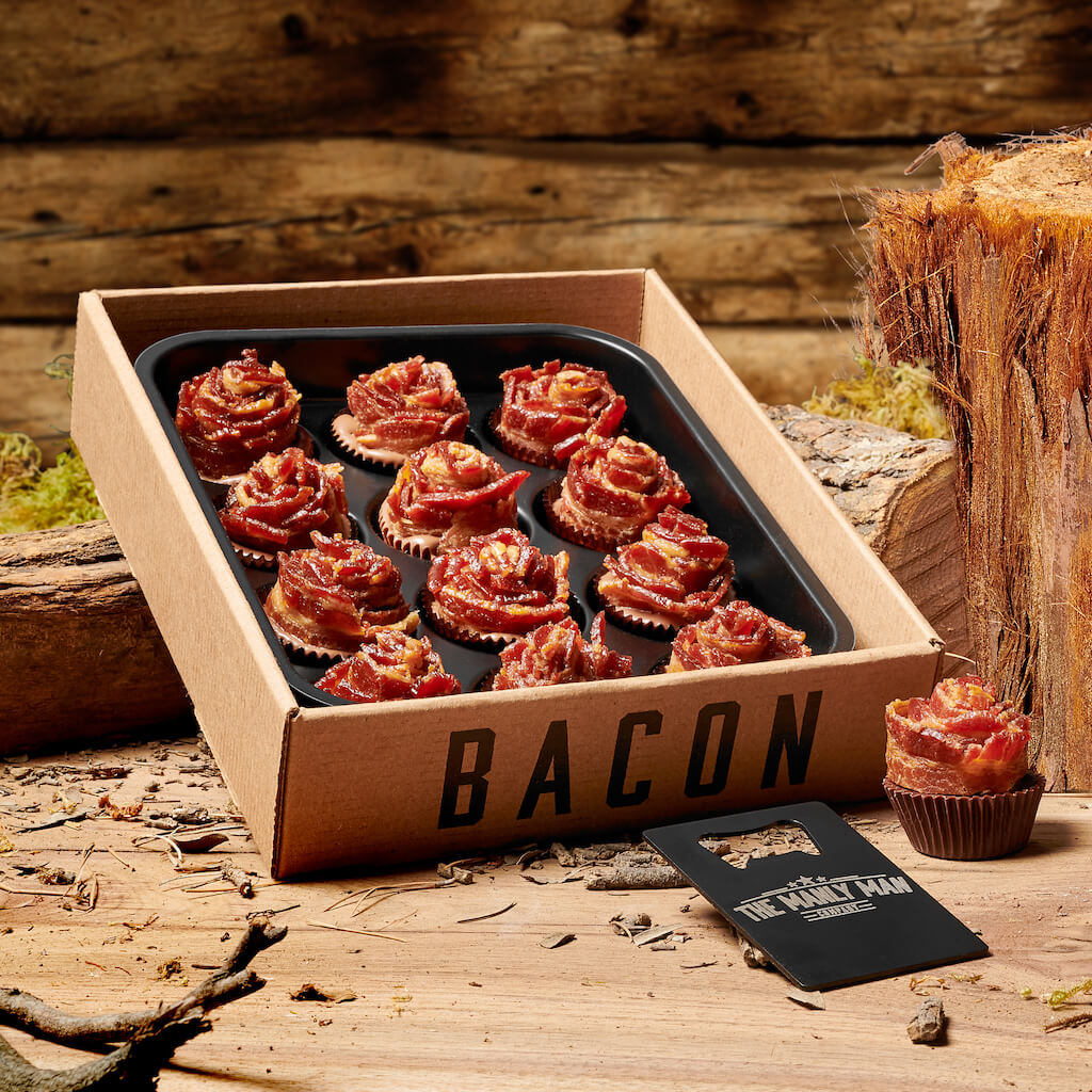Bacon roses bouquet and Man Card bottle opener sitting next to tree stump, in front of log cabin