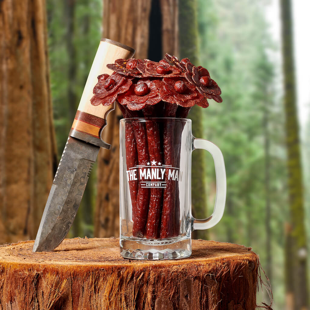 Beef jerky flower bouquet in beef mug and bowie knife, sitting on top of log in a redwood forest