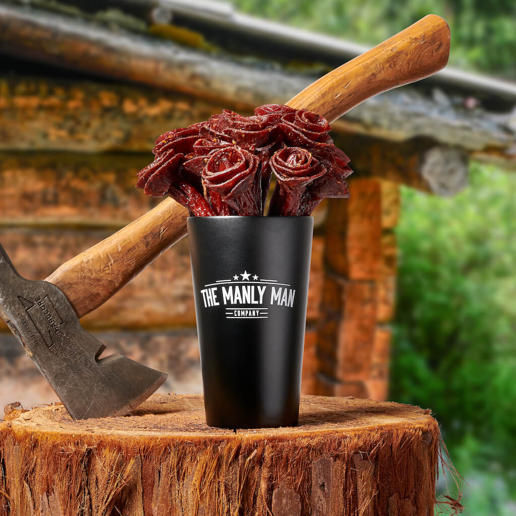 Beef jerky rose bouquet in black steel pint glass and hatchet sitting on a tree stump, in front of a wood cabin