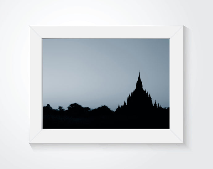 A framed photograph of ruins hung on a white wall.