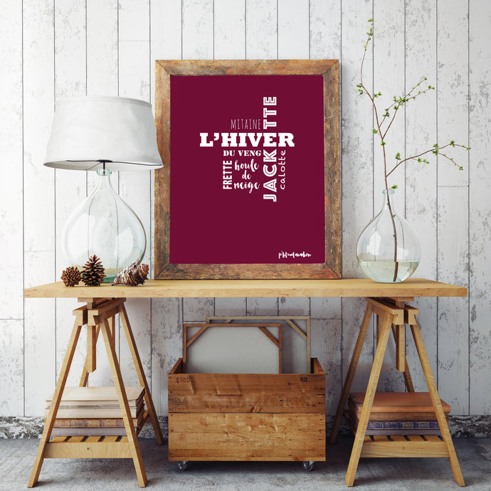 A red framed Acadian words print about winter sitting on a table.